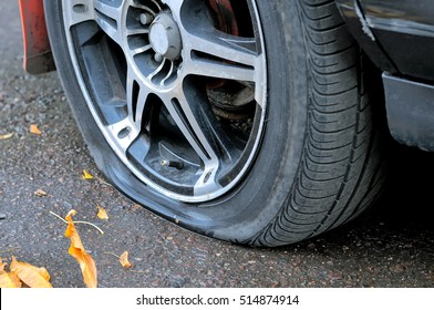Flat tire of a car on the pavement. Side view close up