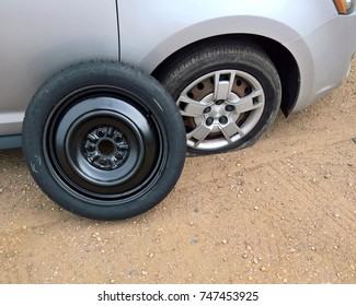 Flat tire (front passenger) with a spare ready to be put on a silver car