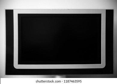 Flat TV panel in niche on a wall. Abstract technology photo. Geometric background with extensive copy space.