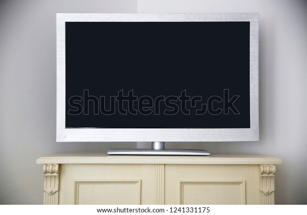Flat TV panel on a chest of drawers with antique-styled decorative elements. Abstract interior or home technology photo. Geometric background with refined black copy space. Hi-tech meets classics.