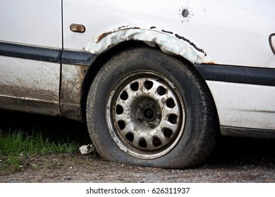 Flat tyre on an old rusty car