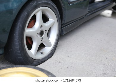 Flat tyre on road. Car tire leak because of nail pounding. Wheel damage on a road.