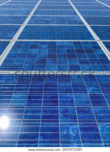 flat view of bright blue solar panels with sunlight and reflections