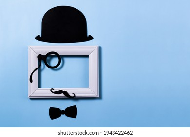 A flat view of a father's Day holiday card. Props photo frames hat, mustache and eyepiece made of cardboard.
