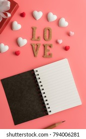 Flat view of notepads  in the centre of valentines hearts and decoration on pink background with copy space. Symbol of love. Happy Valentines Day background.Saint Valentine's Day concept.