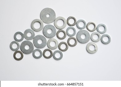 Flat washers for fastening in the contour of the heart. Flat metal washers as background. Used old washers and spring washers with isolated white background for commercial.