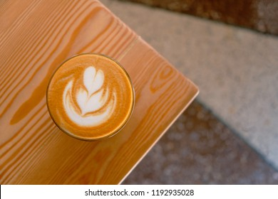 Flat white coffee on the table corner top view. Flat white coffe in transparent glass in a cafe.It is espresso-based coffee drink consisting of espresso with microfoam (steamed milk with fine bubbles)
