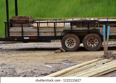 Flatbed holding various sizes of wood for new construction.  Grass and dirt in the background.  Wood planks piled near the truck.
