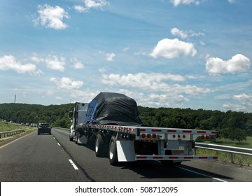 Flatbed semi transporting covered freight