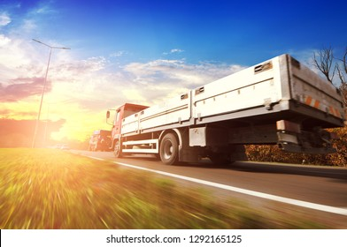 Flatbed truck and cars in motion on the countryside road against sky with sunset