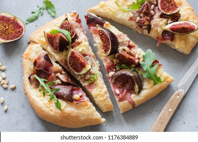 Flatbread with figs, ham, cheese and arugula. Gourmet pizza with prosciutto. Closeup view