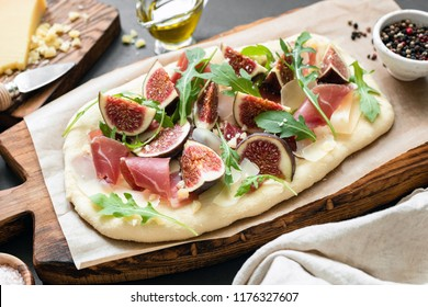 Flatbread pizza with figs, prosciutto and arugula on wooden serving board. Closeup view. Gourmet pizza