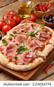 Flatbread pizza with prosciutto, capers and fresh basil leaves on wooden background. Close up view. Italian food concept