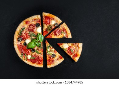 Flatbread pizza  with  slices on black background. Pepperoni Pizza. Copy space. Top view