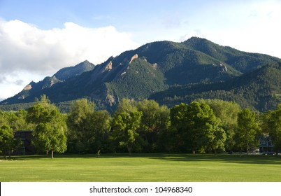 The Flatirons Mountains above Boulder, Colorado, as seen from North Boulder Park on a quiet summer day