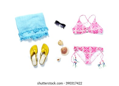 flatlay from above white beach with sandals towel sunglasses camera and bikini pink