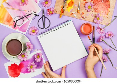 Flatlay with art supplies, artist palette, glasses, flowers and woman's hands holding sketchbook with blank page. Creativity concept, spring/summer floral composition, flaltlay, violet background