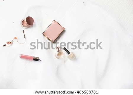 Flatlay of a beautiful fashion bride accessories, sweet and sensual. Wedding make up cosmetic items top view. Veil on white background. Art modern style.