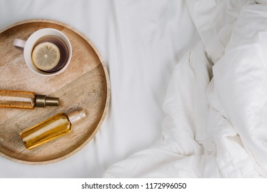 Flatlay of bed with white sheets, blankets and wooden tray with lemon tea and body or hair oils or serums, concept of morning or night skincare