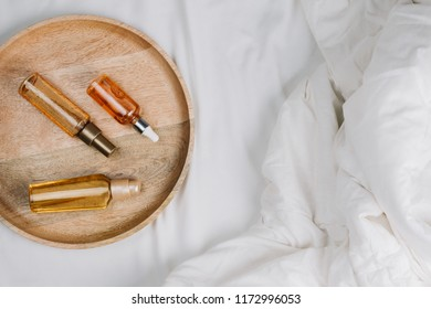 Flatlay of bed with white sheets, blankets and wooden tray with body, face or hair oils or serums, concept of morning or night skincare