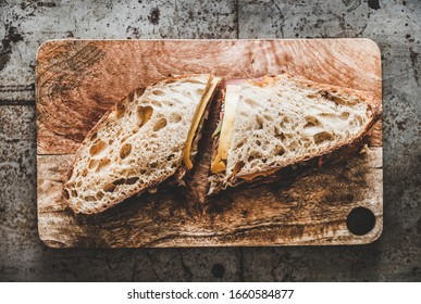 Flat-lay of big Ruben pastrami sandwich in sourdough bread with cheese, pastrami, sauer kraut and pickled cucumber on serving wooden board over rough rustic metal background, top view - Shutterstock ID 1660584877