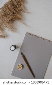 Flatlay blank paper sheet pad, pampas grass, fountain pen, golden ink on beige concrete background. Home office desk workspace. Business, work, lettering, handwriting template. Flat lay, top view.