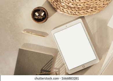 Flatlay of blank screen tablet, notebooks, clips in wooden bowl, straw stand on beige concrete background. Home office desk workspace. Business, work template. Flat lay, top view.