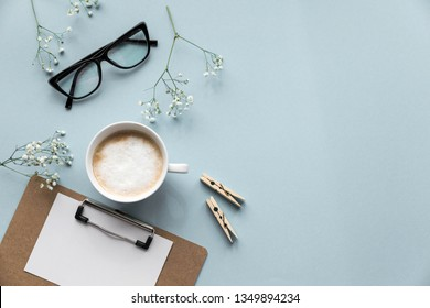 Flatlay blue background office home working space with coffee, paper holder, stickers and phone