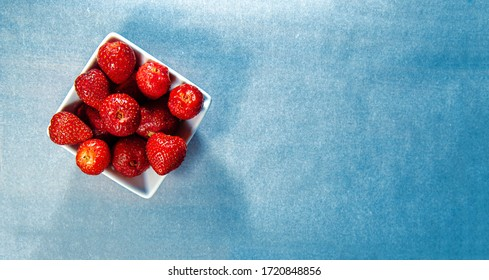 Flatlay a bowl of fresh strawberry, pure and clean minimal blueish concrete background top view modern image with trend colors. Copy space