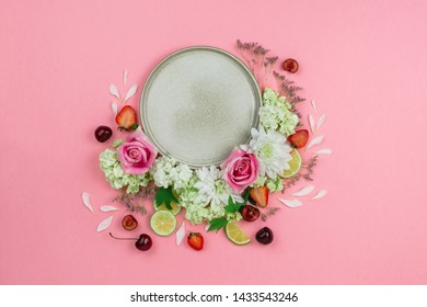 Flatlay of ceramic grey handmade plate with various berries and flowers