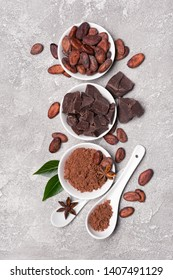 Flatlay of chocolate chunks with cocoa beans and powder for confectionery on gray concrete background