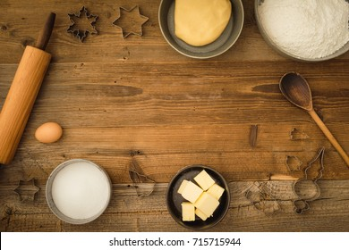 Flatlay collection of tools and ingredients for baking Christmas cookies with copyspace in the center on a dark wooden table. Shot from above