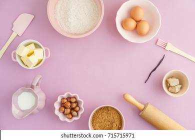 Flatlay collection of tools and ingredients for home baking with copyspace in the center on pink background shot from above