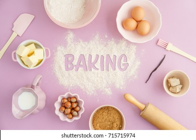 Flatlay collection of tools and ingredients for home baking on pink background with the word baking written in flour in the center. Shot from above