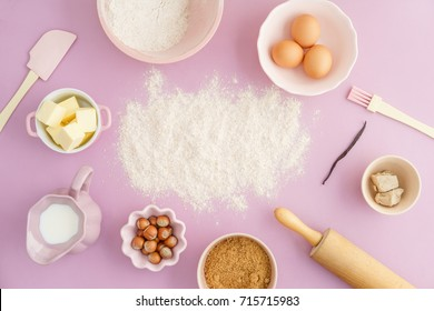 Flatlay collection of tools and ingredients for home baking with Flour copyspace in the center on pink background shot from above