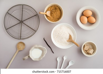 Flatlay collection of tools and ingredients for home baking on light grey background shot from above