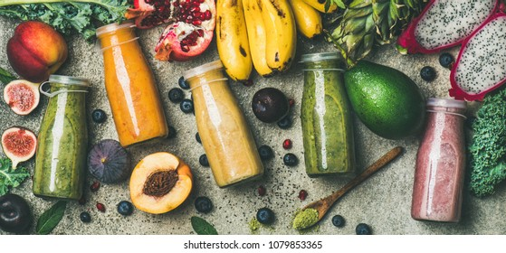 Flat-lay of colorful smoothies in bottles with fresh tropical fruit and superfoods on concrete background, top view. Healthy, vegetarian, detox, dieting breakfast food concept
