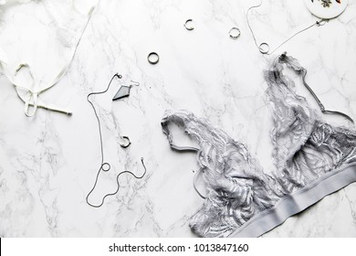 Flatlay composition with female lingerie and jewelry in monochromatic color tone on white marble background with text space.