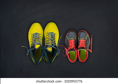 Flatlay composition of fitness sneakers for him and for her on a black background. Concept of healthy lifestyle, sport and activity.