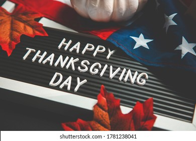 FLatlay composition happy thanksgiving day . american flag, pumpkins and autumn leaves on a black background.