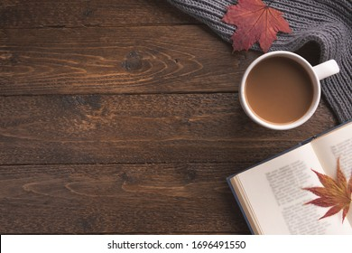 Flatlay composition with knitted scarf, cup of coffe, book, and yellow leaves on wooden desk table. Hygge style, cozy autumn or winter holiday concept. Flat lay, top view, overhead.