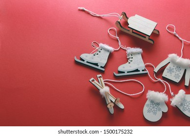 Flatlay composition of wooden christmas decorations-sweater,hat,socks,sledding, ice skating and mittens on red background. Copy space, top view  winter, new year concept.