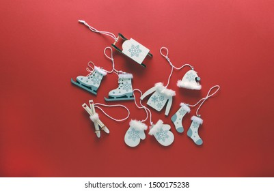 Flatlay composition of wooden christmas decorations-sweater,hat,socks,sledding, ice skating and mittens on red background. Copy space, top view.Christmas, winter, new year concept.