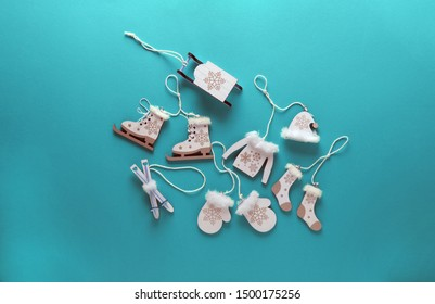 Flatlay composition of wooden christmas decorations-sweater,hat,socks,sledding, ice skating and mittens on blue background. Copy space, top view. winter, new year concept.