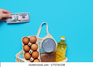 Flatlay, computation. Set of products inside string bag, mens hand giving money cash us dollar banknotes on the blue background. Packaging food from the store. Sunflower oil, eggs, canned food
