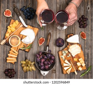 Flat-lay of couple or friends eating and drinking together. Cheese plate served with wine, grapes, fig and honey. Hands holding glasses.