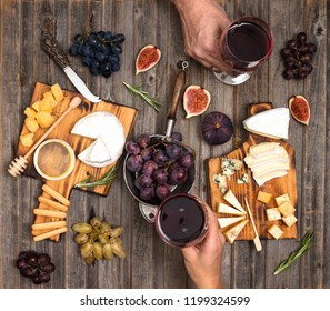 Flat-lay of couple hands or friends enjoying wine, eating and drinking together. People having party, celebrating at wooden rustic table. Cheese plate served with wine, grapes, fig and honey.
