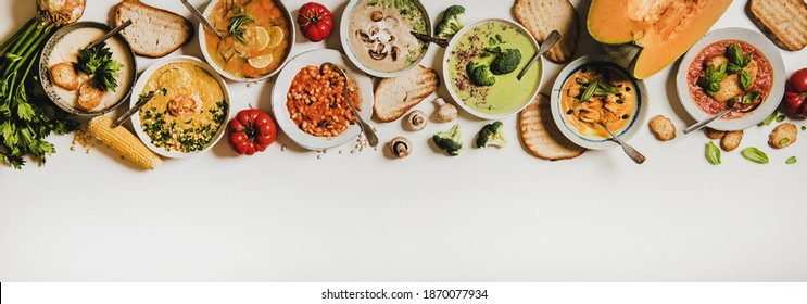 Flat-lay of creamy homemade soup in plates with bread slices over white plain table background, top view, copy space. Autumn Winter creamy vegan soups, vegetarian food menu, comfort food concept