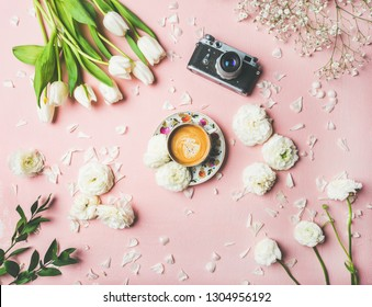 Flat-lay of cup of coffee, film camera, fresh white tulips and buttercup flowers over pink background, top view. Spring vibes or Women's Day holiday concept