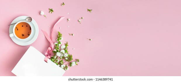 Flatlay cup of tea, white gift bag and spring flowers on a pink background. Beautiful breakfast. Workspace pastel colors. Greeting card with delicate flowers Pink floral background with copy space